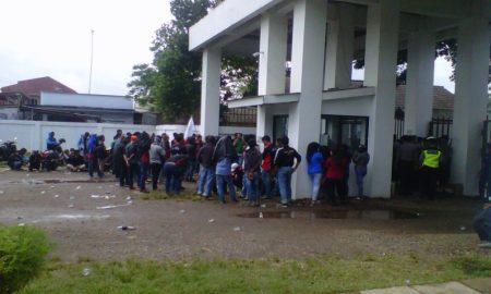 Karyawan unjuk rasa (orasi) didepan pintu gerbang perusahaan dikawal aparat keamanan.