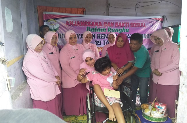 Photo Ketua Bhayangkari Cabang Tapsel Ny. Dewi Irwa beserta rombongan saat melakukan Anjangsana dan para penyandang disabilitas yang di bantu.