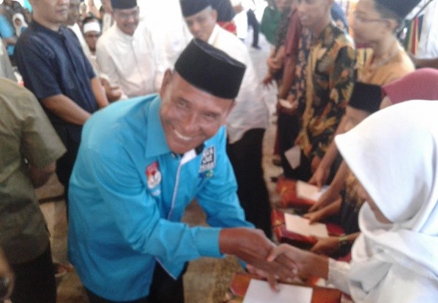 Photo keterangan foto ketua PJI Rohil H.Dahrin,S.Sos memberikan santuanan anak yatim.