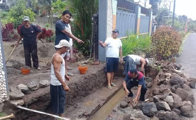 Photo Pendeta Sutriyo saat meletakkan batu pertama perbaikan bahu jalan dan Pembuatan plat dekker di pintu masuk perumahan pendeta GKJW Tulungrejo yang dikerjakan secara gotong royong